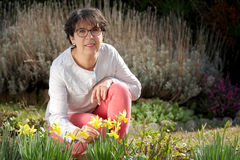 Brunette mature woman in her garden with daffodils Royalty Free Stock Photography