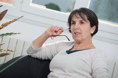 Brunette mature woman relaxing in the sofa. Brunette mature woman relaxes in the sofa at home Royalty Free Stock Photos