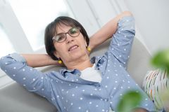 Brunette mature woman relaxing in the sofa. Brunette mature woman relaxes in the sofa at home Stock Photos