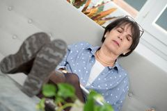 Brunette mature woman relaxing in the sofa. Brunette mature woman relaxes in the sofa at home Stock Photography
