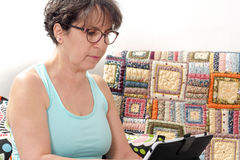 Brunette mature woman using tablet at home Royalty Free Stock Image