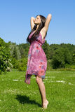 Brunette on the meadow. Pretty young woman stretching to the sky Stock Image