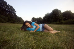 Brunette in meadow. An early twenties caucasian female relaxes on a clear afternoon in a Connecticut, USA, meadow royalty free stock image