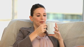 Brunette middle aged lady drinking a cup of coffee stock video