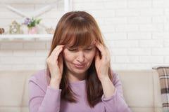 Brunette middle aged woman having headache on home background. Menopause. Brunette middle aged woman having headache on home background Stock Image