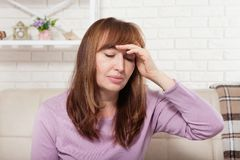 Brunette middle aged woman having headache on home background. Menopause Stock Image