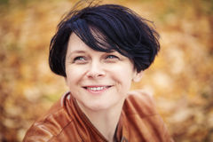 Brunette middle aged woman outside in autumn park Royalty Free Stock Photos