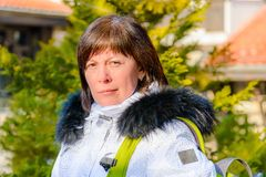Brunette middle-aged woman in a stylish white jacket with fur hood Stock Photos