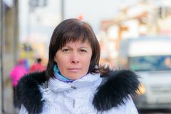 Brunette middle-aged woman in a stylish white jacket with fur hood Stock Images
