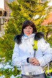 Brunette middle-aged woman in a stylish white jacket with fur hood Royalty Free Stock Images