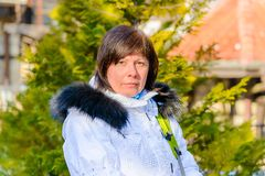 Brunette middle-aged woman in a stylish white jacket with fur hood Stock Photography
