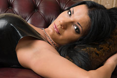 Brunette mistress. A brunette lady mistress lying on the leather couch and looks towards stock images