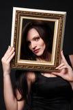 Brunette mit Bilderrahmen. Lizenzfreie Stockfotografie