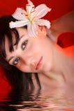 Brunette mit Blumen der weißen Lilie im Wasser Lizenzfreies Stockbild