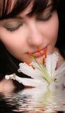 Brunette mit Blumen der weißen Lilie im Wasser Lizenzfreies Stockfoto
