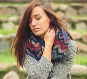 Brunette mit dem Fliegenhaar, das gegen den Hintergrund von Herbstbäumen aufwirft Stockfotografie