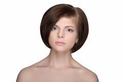 Brunette mit dem kurzen Haar, welches die Kamera auf Weiß lokalisiert betrachtet Stockbild