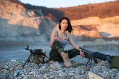 Brunette mit einem Maschinengewehr auf einem Hintergrund von Bergen Stockfotografie