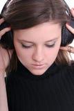 Brunette mit Kopfhörern meditiert Stockbilder