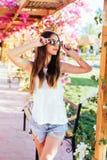Brunette mit langem Haarmädchen kurz gesagt, WhiteThemd und modische Sonnenbrille auf einer Bank in einem Freiluftcafé an einem s stockbild