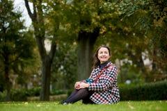 Brunette mit süßem Lächeln sitzt auf grünem Gras im Park Stockbilder