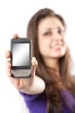 Brunette with mobile phone or PDA. Young hispanic girl holding a mobile phone or PDA to the viewer Royalty Free Stock Photography