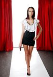 Brunette model on the catwalk. With red drapes in the background Royalty Free Stock Photography