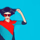 Brunette model with fashion haircut and sunglasses on a blue bac Royalty Free Stock Photos