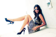 Brunette model at fashion sitting. Funny female model at fashion with high heels sitting on the floor Stock Photo