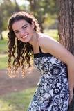 Brunette model leaning against tree. Smiling royalty free stock photo