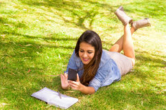 Brunette model lying on grass, feet up in air Royalty Free Stock Photography