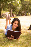 Brunette model lying on grass happily reading a Stock Image