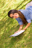 Brunette model lying on grass happily reading a Stock Images