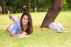 Brunette model lying on grass inside park smiling Stock Images