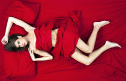 Brunette Model Lying on Red Bed Royalty Free Stock Images