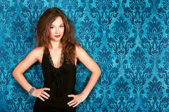 Brunette model posing against blue vintage wall smiling fashion Royalty Free Stock Photo