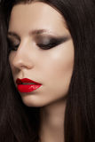 Brunette model with red gloss lips, fashion make-up and long straight hair Royalty Free Stock Images