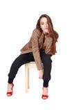 Brunette model sitting on stool Stock Image