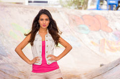 Brunette model wearing pink top, white vest and Royalty Free Stock Image
