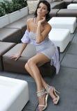 Brunette model wearing sexy minidress sitting on the sofa Royalty Free Stock Image