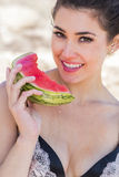 Brunette-Modell auf dem Strand, der eine Wassermelone isst Lizenzfreies Stockfoto