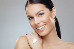 Brunette with moisturizer on her hand Stock Photography