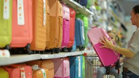Brunette Mother with Her Little Daughter Choosing Travel Bags. Cute Girl is Sitting in Supermarket Cart, Young Woman stock video footage