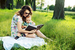 Brunette mother reading a fairy tale for her child Royalty Free Stock Images