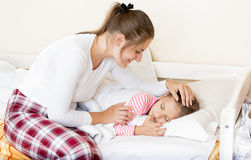 Brunette mother waking up sleeping daughter at morning Stock Photo