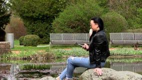 Brunette nahe dem See mit einem Telefon stock footage