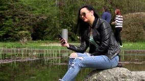 Brunette nahe dem See mit einem Telefon stock video