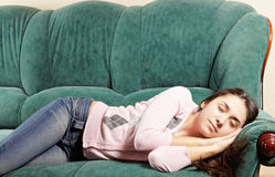 Brunette napping on green sofa Stock Photography