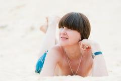 Brunette nas calças de brim que encontram-se na areia. Foto de Stock
