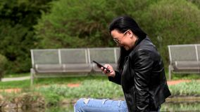 Brunette near the lake with a phone. Sitting on a stone stock video footage